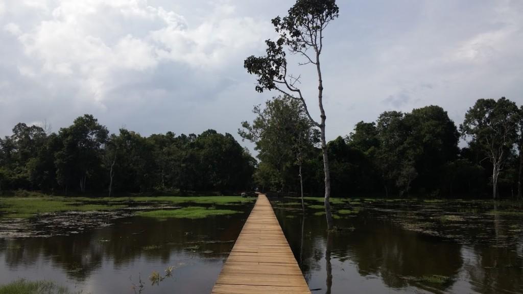 Camino de madera sobre el río hacia el Templo Neak Pen